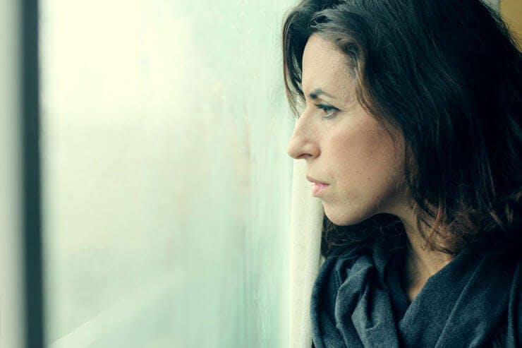 An anxious woman looking out the window of her apartment