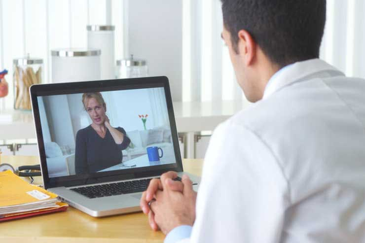 A doctor sees a patient on a video call, telemedicine