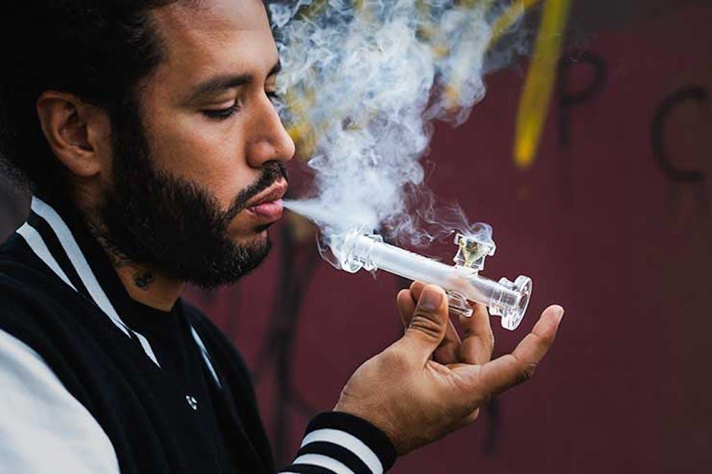 A man smokes marijuana from a glass pipe
