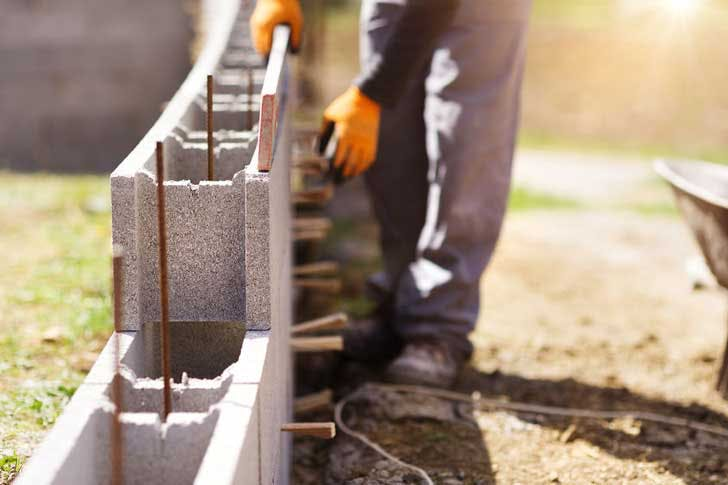 A construction worker lays cinder blocks