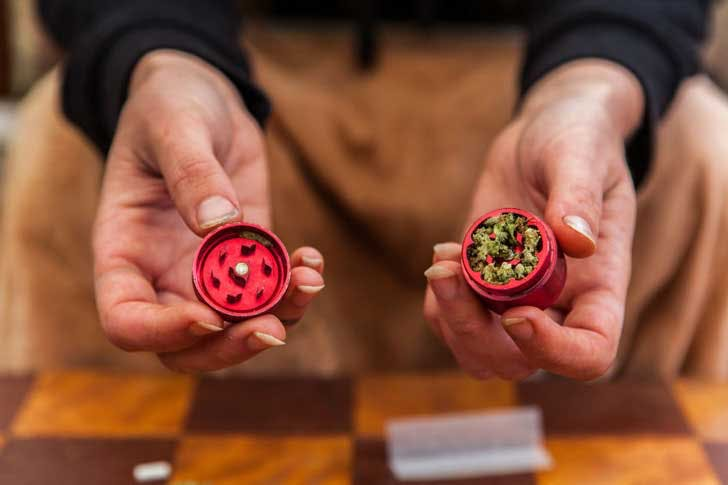 Breaking up cannabis in a grinder