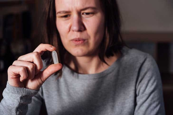 A woman examines a suppository
