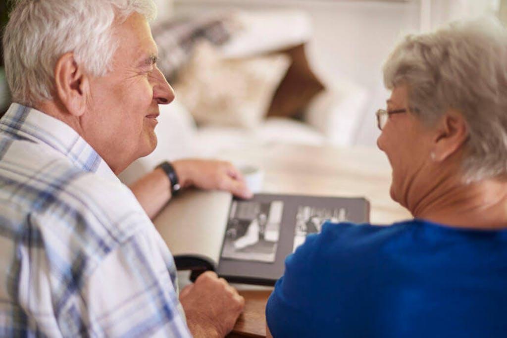 Casal idoso olha álbum de fotos
