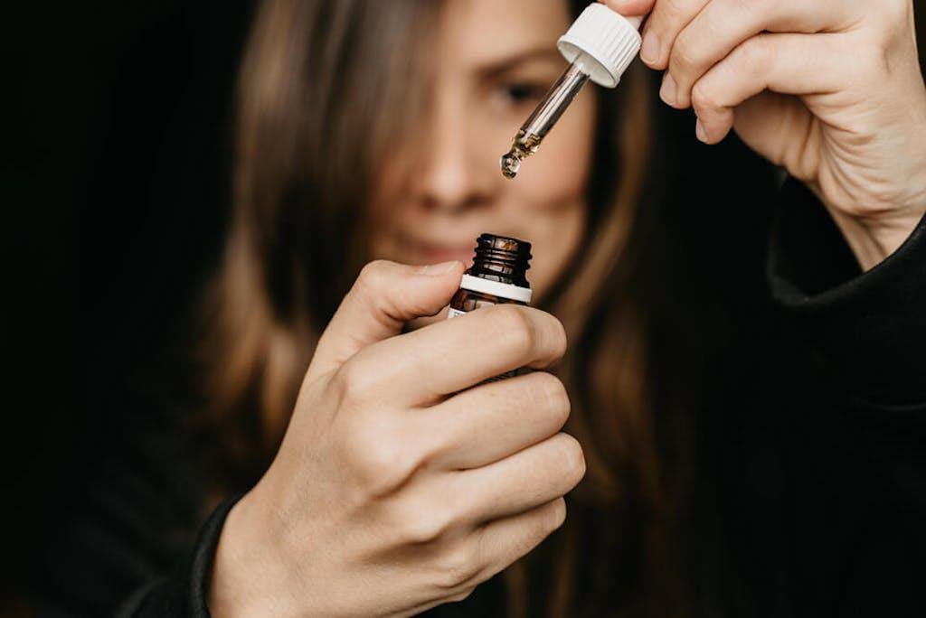 A woman about to take CBD oil