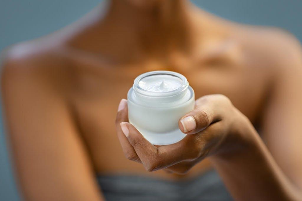 A woman holds a jar of CBD cream