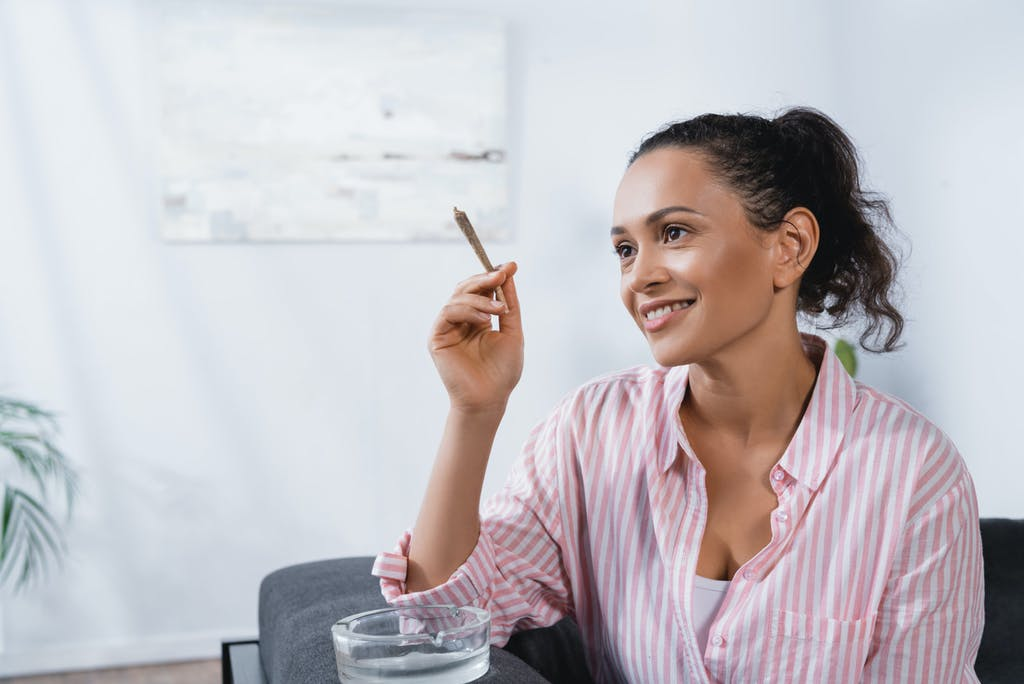 Young woman smiling and holding a joint next to an ashtray