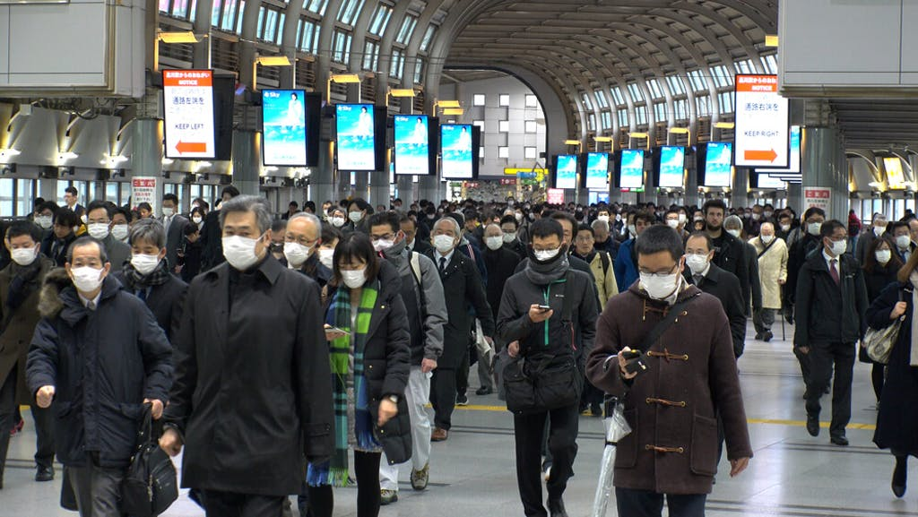 Crowds of people walking at Shinagawa station in busy morning rush hour, Tokyo, Japan.