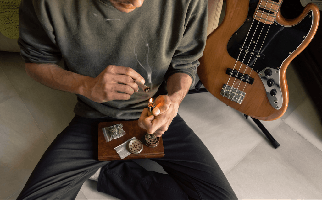 Man sitting on the floor smoking a marijuana joint at home after playing the bass.