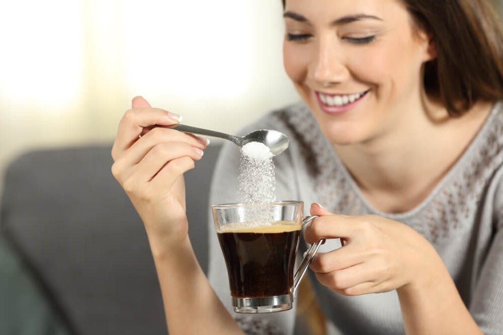 A woman pours a teaspoon of sugar into her coffee