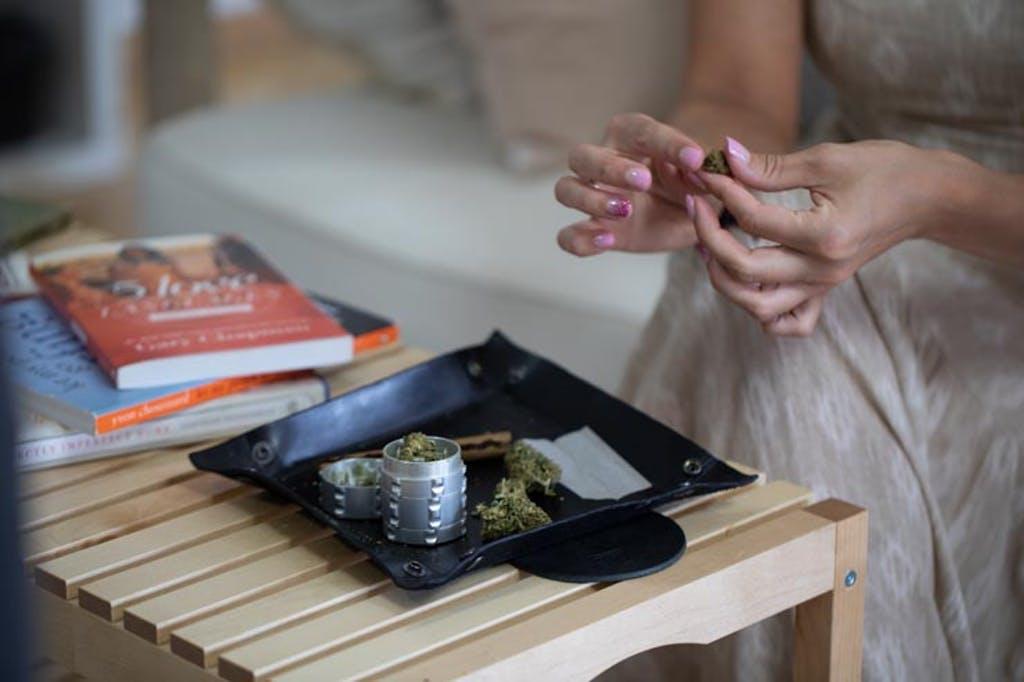 Mulher enrola um baseado com a ajuda de um grinder (moedor de erva)