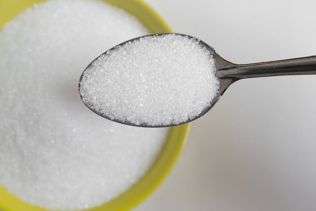 Spooning white sugar out of a yellow bowl