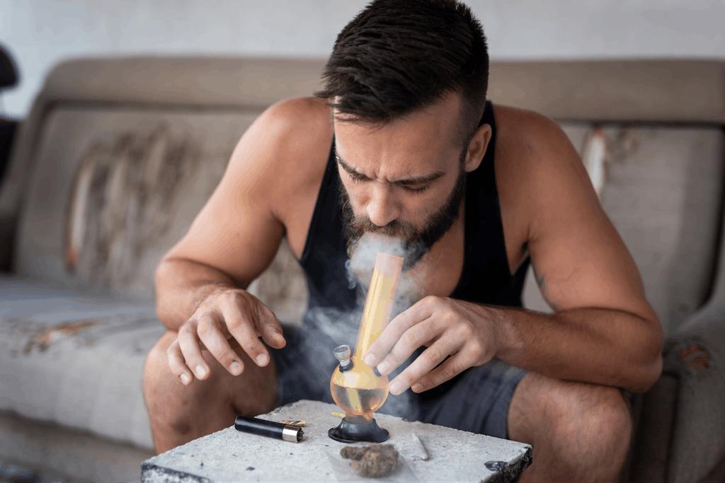 A man smoking cannabis from a glass bong.