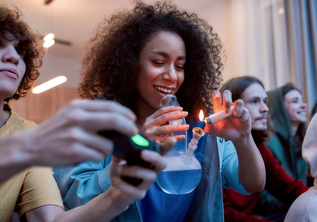 Woman lighting marijuana in a glass bong.