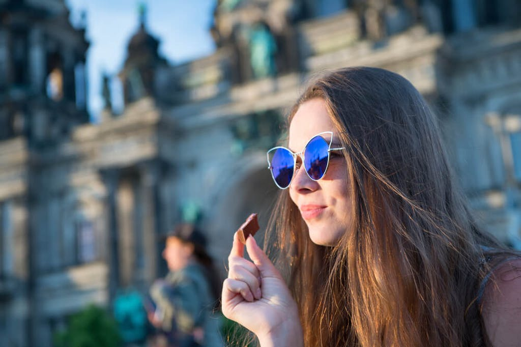 A woman eats a piece of chocolate outside on a nice day in Berlin