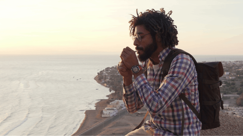 Man smoking joint with cannabis sitting on a cliff at sunrise