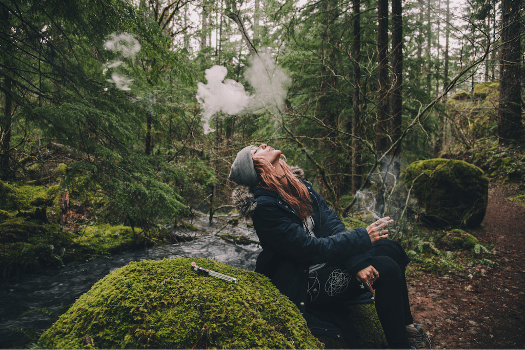 Woman smoking cannabis while hiking in the woods