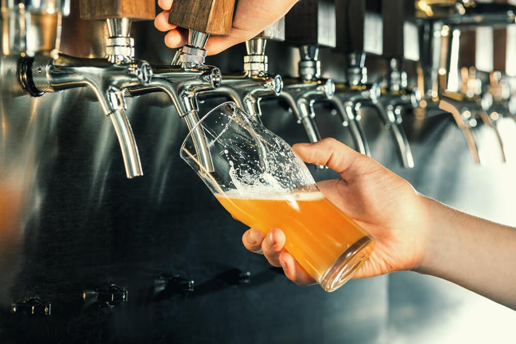A bartender pours a beer from the tap