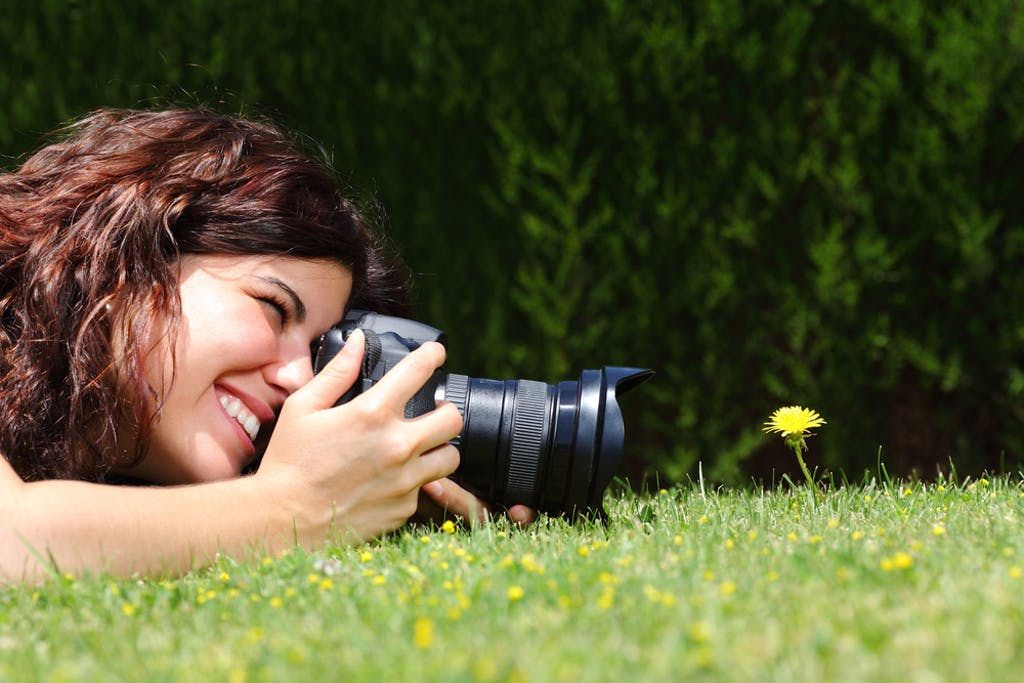 A woman takes a macro hotograph of a flower in the park