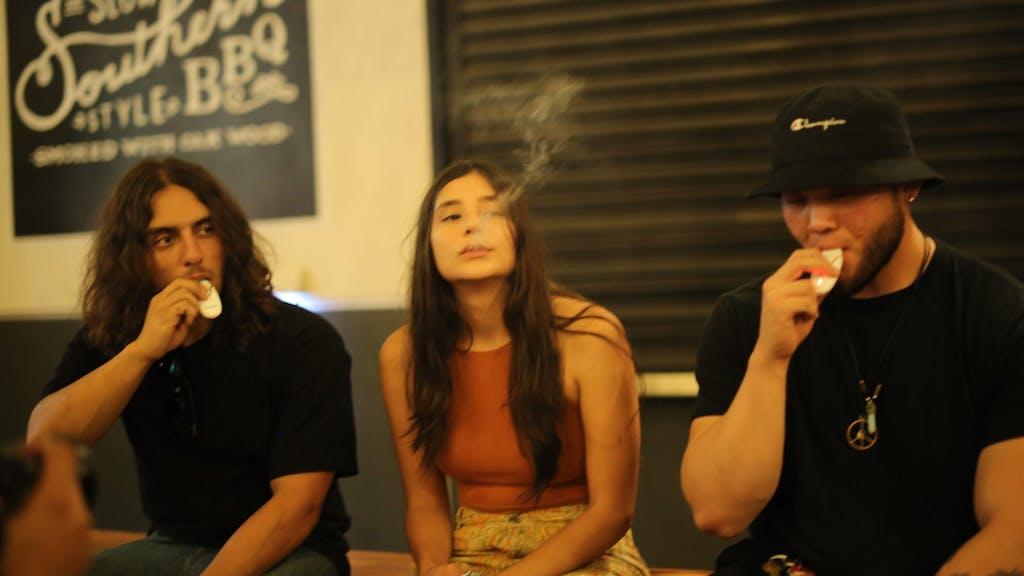Three friends use their Basiq vaporizers outside a club