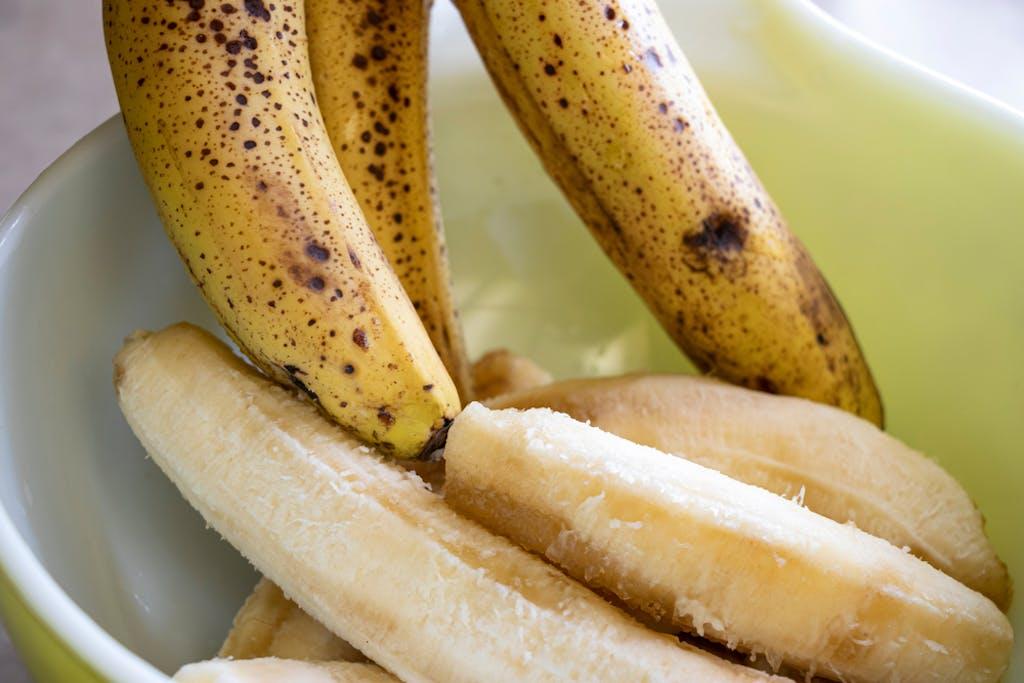 Putting bananas into a bowl to smush while preparing cannabis banana bread