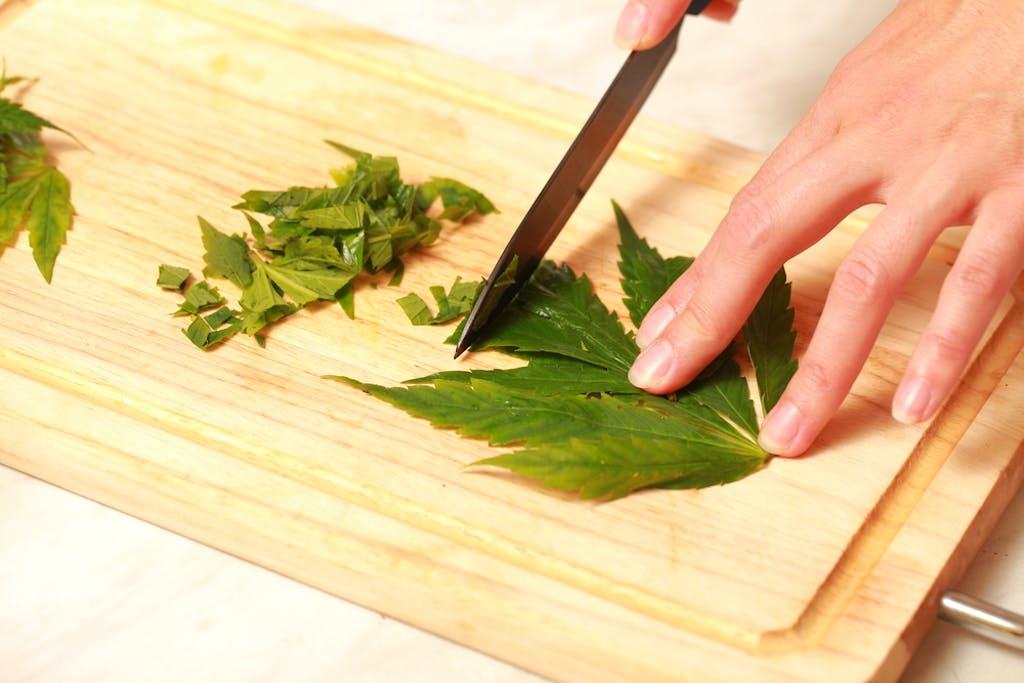 Cutting cannabis leaves on a cutting board