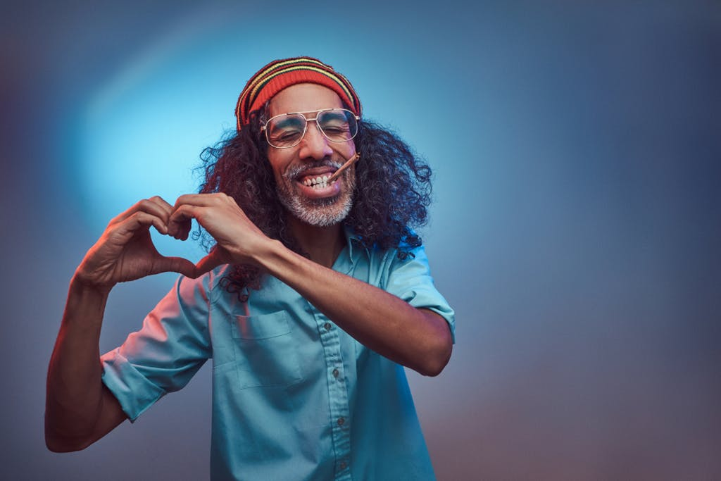 African Rastafarian smokes weed and shows heart symbol and shape with hands.