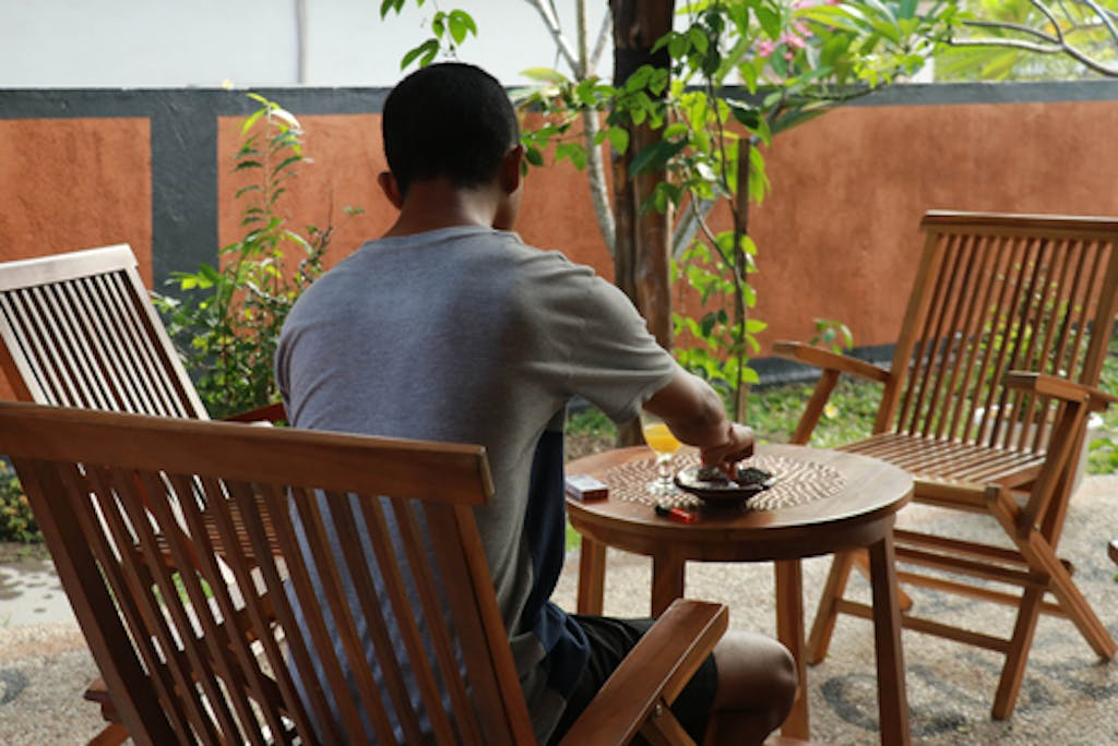 Asian young man enjoying his morning on a hotel terrace, while on vacation