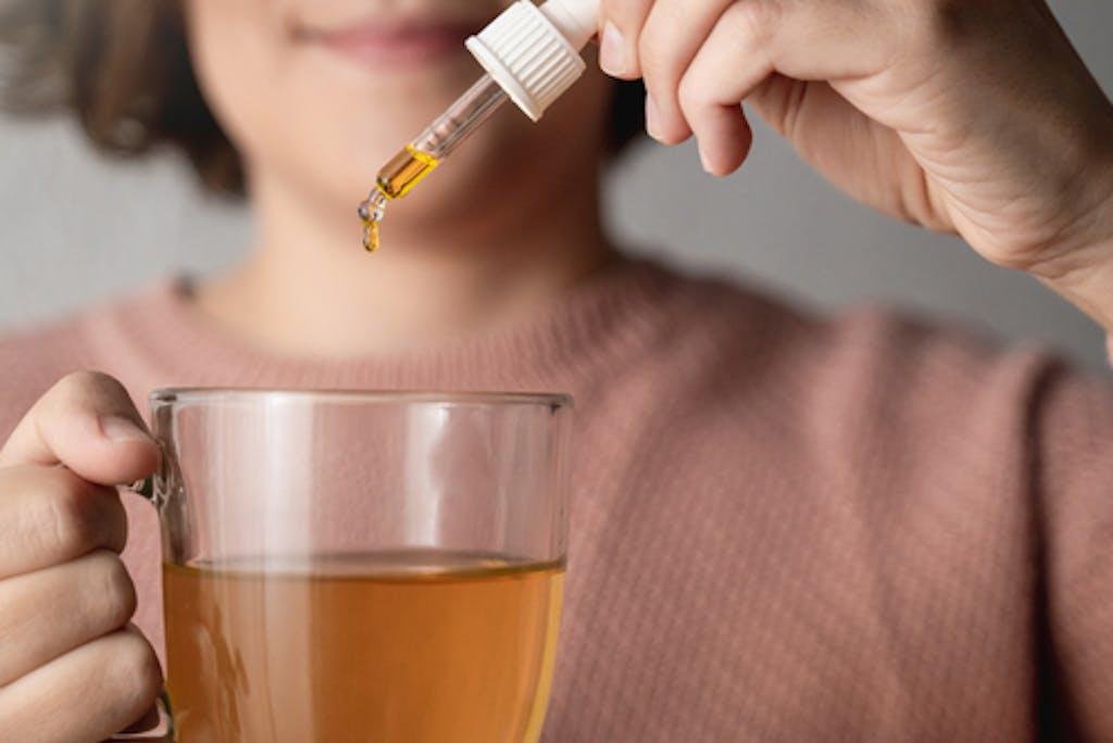 Woman using a cannabis tincture in tea