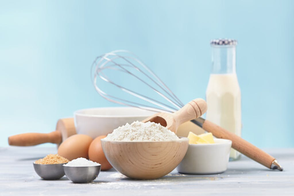 Ingredients and tools to make a sugar cookies, including flour, butter, sugar,eggs