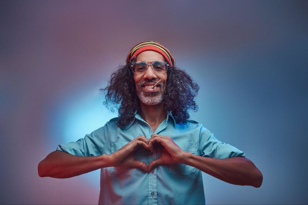 African Rastafarian smokes weed and showing heart symbol and shape with hands