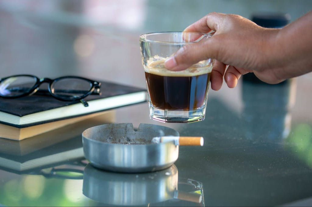 A hand holding a glass of black coffee and cigarette smoking on the table with the books and the glasses