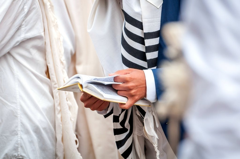Orthodox hassidic Jews pray in a holiday robe and tallith